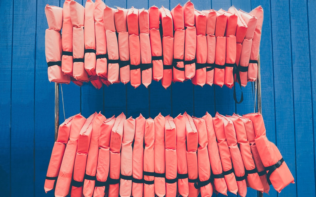 life jackets hung on the side of a blue barn near a lake
