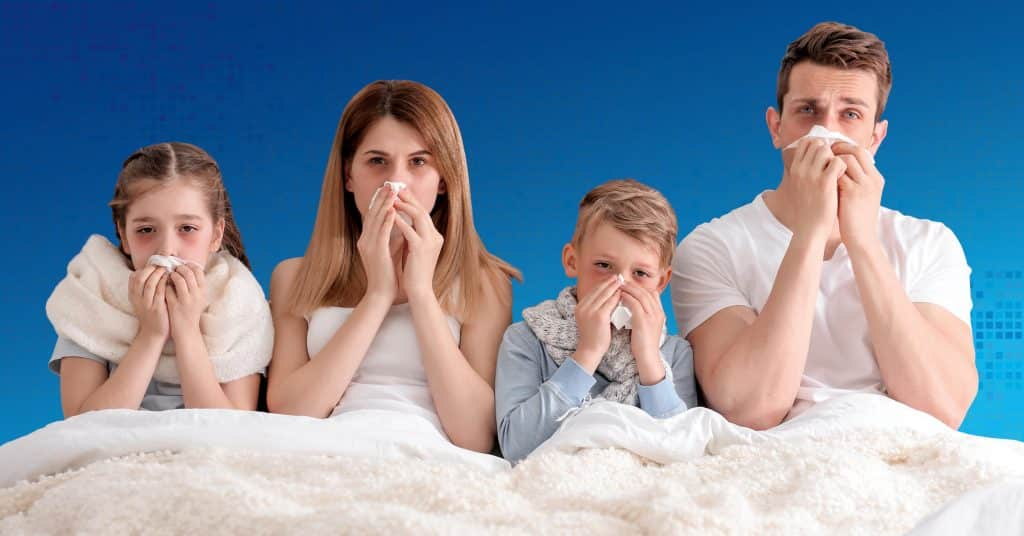 a sick family of four all blow their noses in bed